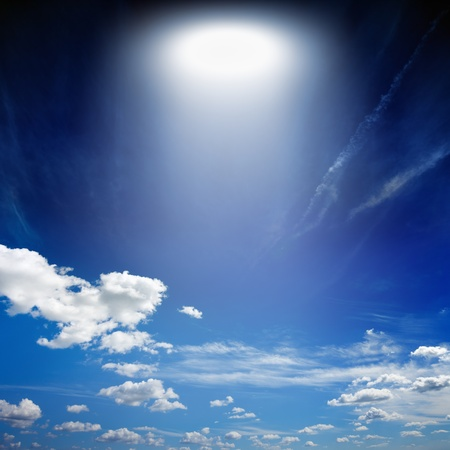 Abstract fantastic background - blue sky, white clouds, bright spotlight from above