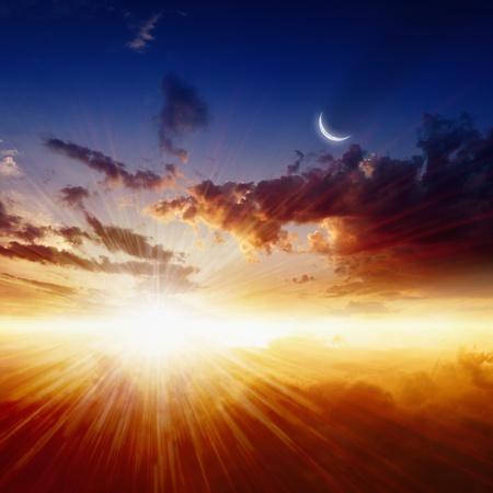 Prachtige natuur achtergrond - rode zonsondergang, felle zon, de maan in het donker blauwe hemel, gloeiende horizon