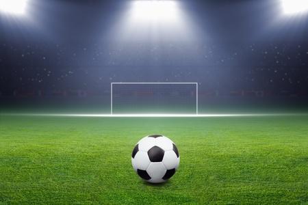 Soccer ball on green stadium, arena in night illuminated bright spotlights, soccer goal