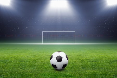 Soccer ball on green stadium, arena in night illuminated bright spotlights, soccer goal