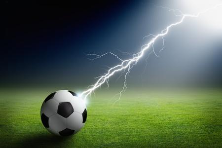 ball lightning: Sports background - soccer ball on green stadium struck by lightning, bright light from spotlight