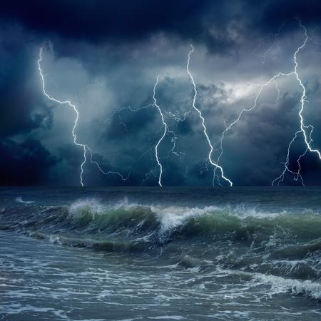 Dramatic nature background - lightnings in dark sky, stormy sea, big waves Stock Photo
