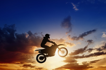 Active sports background - jumping motorcircle rider silhouette, beautiful sunset photo
