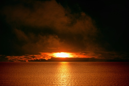 Dramatic apocalyptic background - red sunset over sea, dark clouds photo