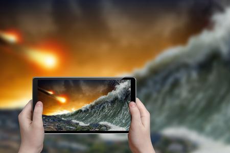 tsunami: Abstract tablet pc in hands photographs giant tsunami waves crashing small coastal town and asteroid impact Stock Photo