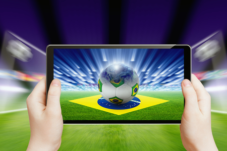 Technology, sports background - tablet pc in hands, soccer ball, sports game online, soccer online, brazil flag, brazil soccer, brazil soccer online.  photo