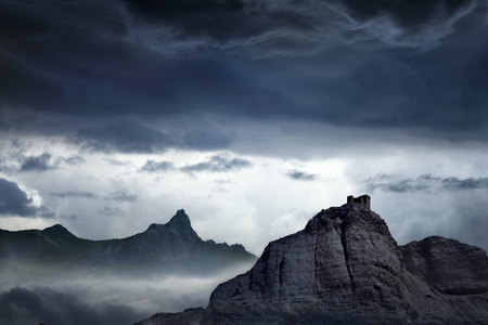 Nature background - dark stormy sky above mountains, fortress on top of rock Stock Photo - 30167966