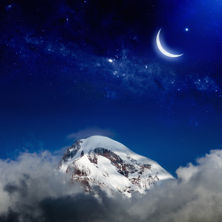 Moon and stars above snowy peak of mountain.