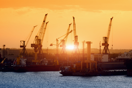 sea seaport: Transportation and logistic background - freight cargo ships and cranes in seaport on sunset