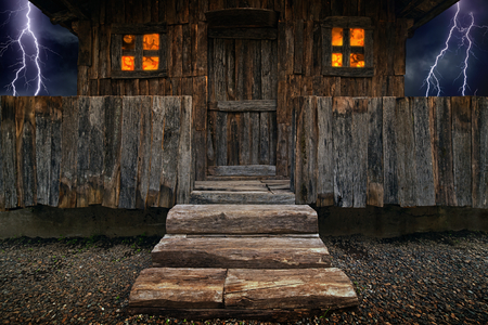 lightnings: Old brown wooden hut with glowing windows, fence and big wooden stairs, dark stormy sky with lightnings