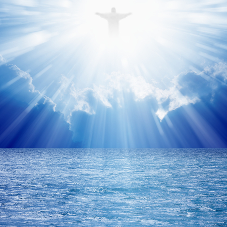 Jezus: Chrystus sylwetka w bluesowych niebie nad morzem, jasne światło z nieba Zdjęcie Seryjne