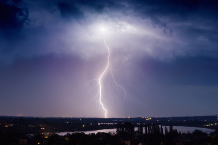 Huge lightning from dark stormy sky strikes small town 写真素材