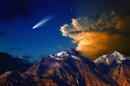Beautiful nature background - bright comet in dark blue sky with stars, mountain with snowy peaks, red light from sunset illuminates mountains, glowing clouds