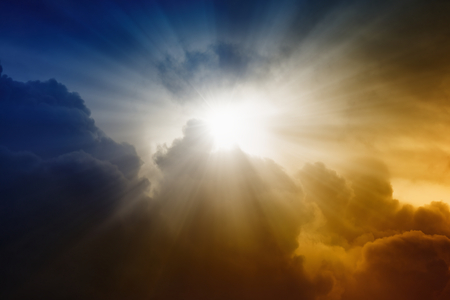 Religious background - bright sunlight from dark red and blue sky, rays of hope
