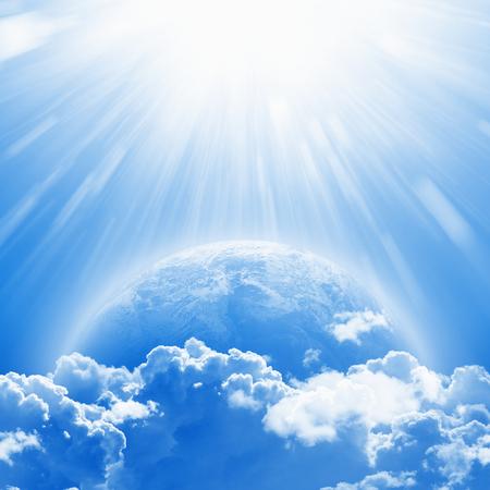 4월 22일 국제 어머니 지구의 날, 흰 구름 위에서 밝은 햇빛에 푸른 행성 지구. 스톡 콘텐츠