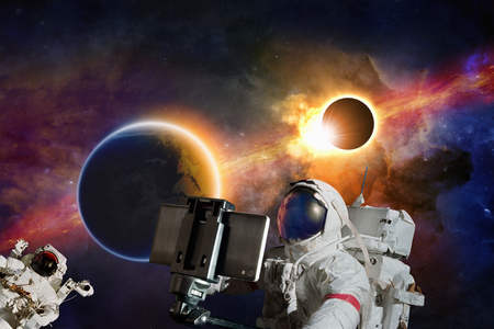 self discovery: Astronaut taking selfie photo in outer space, planet Earth and full solar eclipse in space.