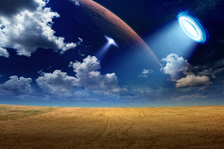 scientific farming: Sci-fi background - UFO shines spotlight on wheat field, aliens invasion. Stock Photo