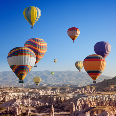 Beautiful colorful hot air balloons flying in clear morning sky above unusual rocky landscape in Cappadocia, Turkey Reklamní fotografie