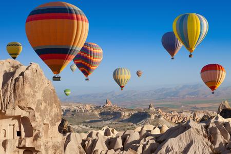 Aantrekkelijkheid amazing - heteluchtballonnen vliegen boven ongebruikelijk rotsachtige landschap in Cappadocië, Turkije