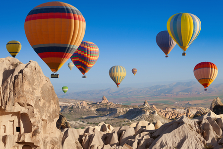 Amazing attraction - hot air balloons flying above unusual rocky landscape in Cappadocia, Turkey