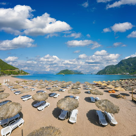 resort beach: Beautiful beach in popular Turkish holiday resort town Icmeler, Turkey. Empty beach loungers with umbrellas on beach at clear blue sea.