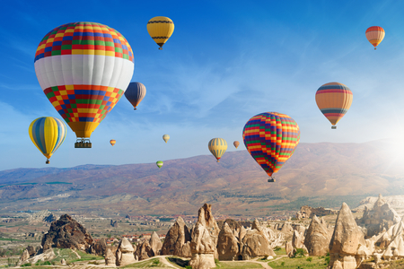 Hot air ballooning is most amazing attraction and adventure in Kapadokya. Colorful hot air balloons flies in morning above unusual rocky landscape in Cappadocia, Turkey