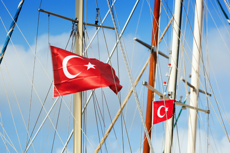 sways: Red turkish flags with star and crescent sways in wind on mast of yachts in sunny day
