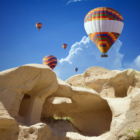 hand carved: Hand carved rooms in limestone rocks near Goreme, Cappadocia. Colorful hot air balloons flies in blue sky in Kapadokya, Turkey