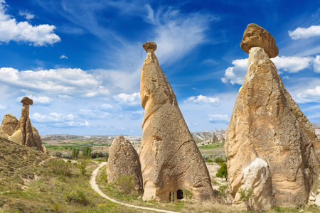 hand carved: Beautiful sunny day with blue sky and white clouds in Cappadocia. Rocks looks like mushrooms with hand carved room near Chavushin in Cappadocia, Turkey