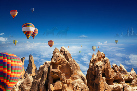 Beautiful collage of symbols of Cappadocia - flying hot air balloons, hand carved rooms in unusual rock formation, two running horses on horizon in Kapadokya, Turkey