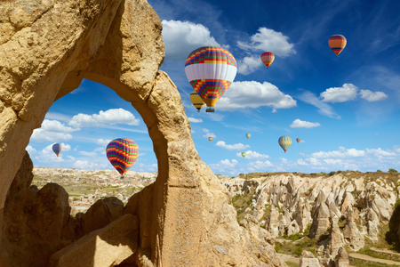 hand carved: Hand carved arch in limestone rock in Goreme National Park, Cappadocia. Colorful hot air balloons flies in blue sky in Kapadokya, Turkey