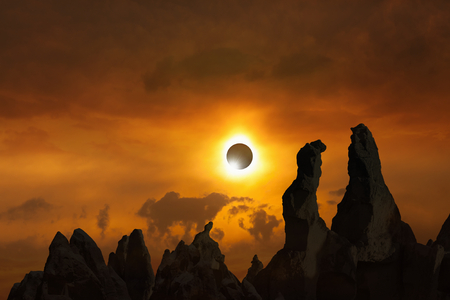 Total solar eclipse is amazing mysterious natural phenomenon when Moon passes between planet Earth and Sun. Silhouettes of high rocks on red glowing sky.