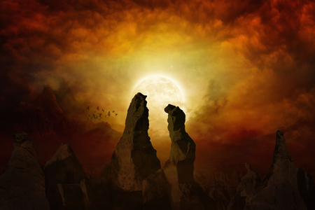 Dramatic mystical background - rising bloody red full moon, silhouettes of high rocks on red glowing sky. Stock Photo