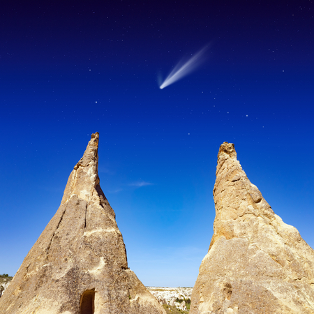 Amazing nature background - bright comet in dark blue sky with stars, two conical rocks Stock Photo