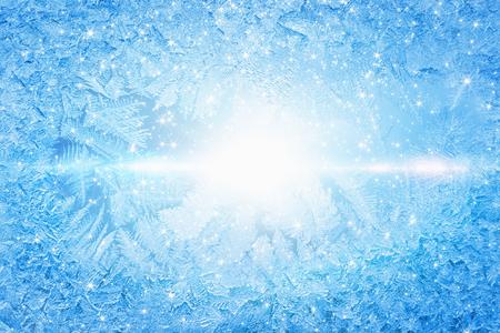 Blue winter background - frozen icy window glass, cold sunny weather, bright sun shines through frozen window