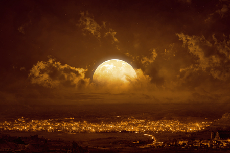 Dramatic mystical background - rising yellow full moon in glowing sky.