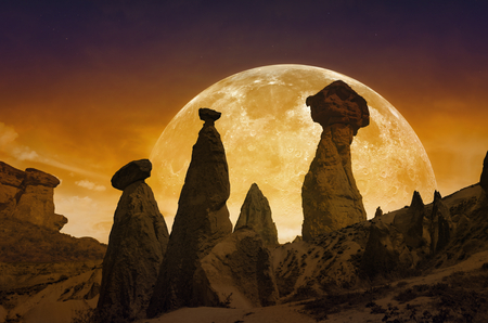 Scenic mystical background - rising bloody red full moon, silhouettes of mushroom rocks on red glowing sky. Stock Photo