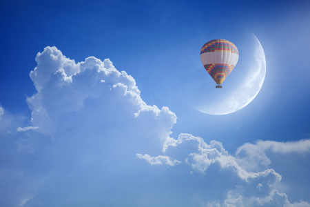 come up to: Idyllic heavenly background - colorful hot air balloon rise up into blue sky above white clouds to new moon. Dream come true concept.