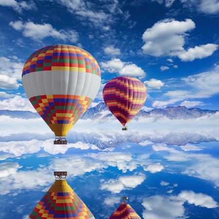Colorful hot air balloons flies above calm lake, white clouds in blue sky, high mountains on horizon