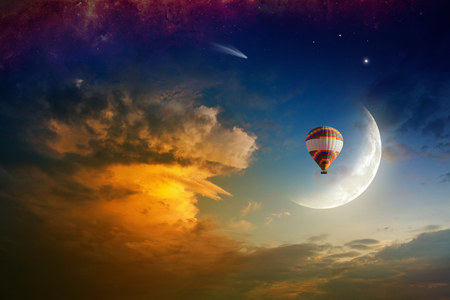 Colorful hot air balloon rises very high in sunset sky above glowing clouds. Crescent, comet and bright stars in blue sky. Dream come true concept. Elements of this image furnished by NASA