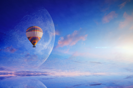 Amazing heavenly picture - colorful hot air balloon in blue sunset sky with rising full moon. Dream come true concept. Elements of this image furnished by NASA. Stock Photo
