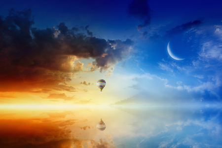 Idyllic heavenly background - colorful hot air balloon flies in sunset sky above calm sea. Glowing red horizon and crescent in blue sky.
