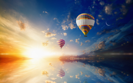 Idyllic heavenly background - two colorful hot air balloons flies in sunset sky above calm sea. Bright sun, glowing horizon and crescent in blue sky.