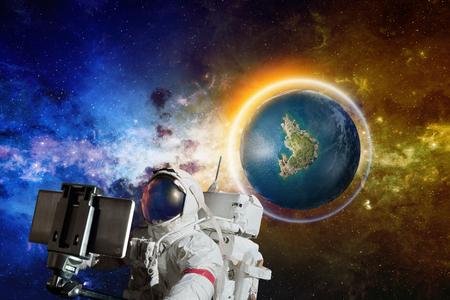 Astronauta que toma la foto del selfie en espacio cerca del planeta Earth-like descubierto con agua líquida y protector que brilla intensamente. Elementos de esta imagen proporcionados por la NASA