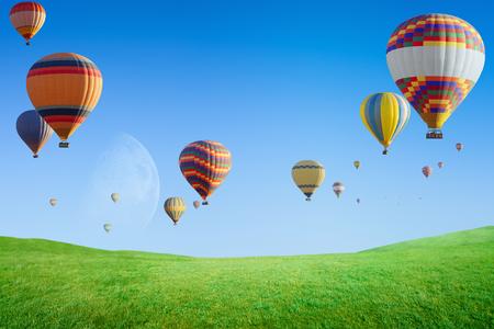 Ballons à air chaud volant dans le ciel bleu clair au-dessus du champ d'herbe verte, grande lune se levant au-dessus de l'horizon. Éléments de cette image fournie par la NASA