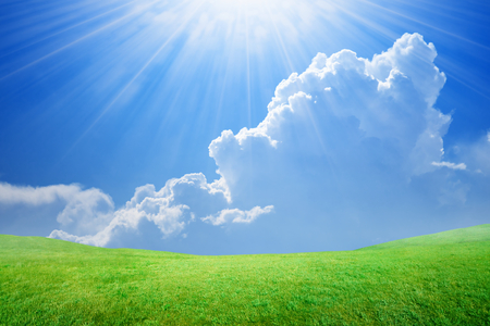 Peaceful idyllic background - beautiful blue sky with bright sun and white clouds, light from heaven, green grass field