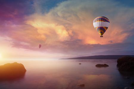 horizonte: Increíble fondo celestial - dos coloridos globos de aire caliente vuela en brillante cielo de puesta de sol sobre el mar tranquilo