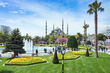 famous people: Istanbul, Turkey - April 22, 2017: Aerial view of Sultanahmet district of Istanbul, Turkey. Walking people, green grass field and fountain near famous landmark Blue Mosque.