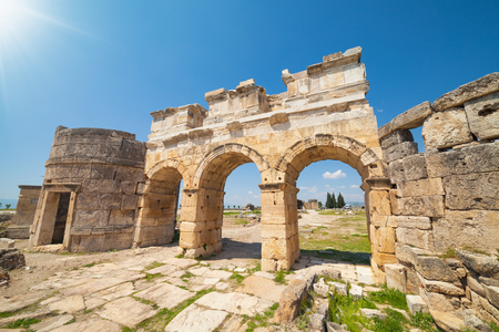 Wide angle view of triple arch Gate of Domitian in Hierapolis ancient city adjacent to modern Pamukkale in Turkey