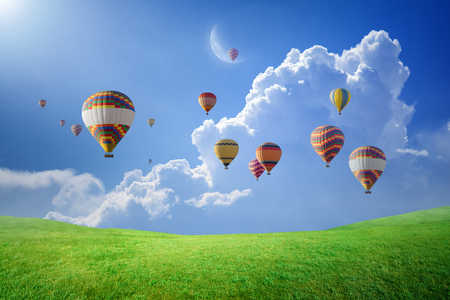 Peaceful heavenly background - colorful hot air balloons rise up into blue sky with white clouds above green field to new moon. Elements of this image furnished by NASA Imagens